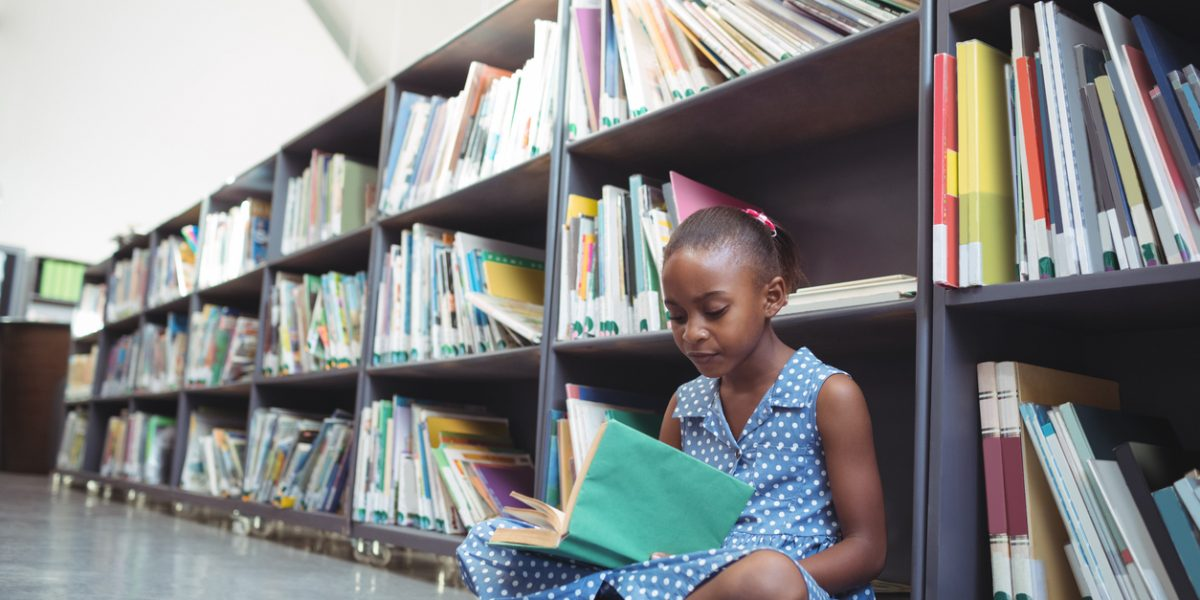 Girl reading book by shelf in library