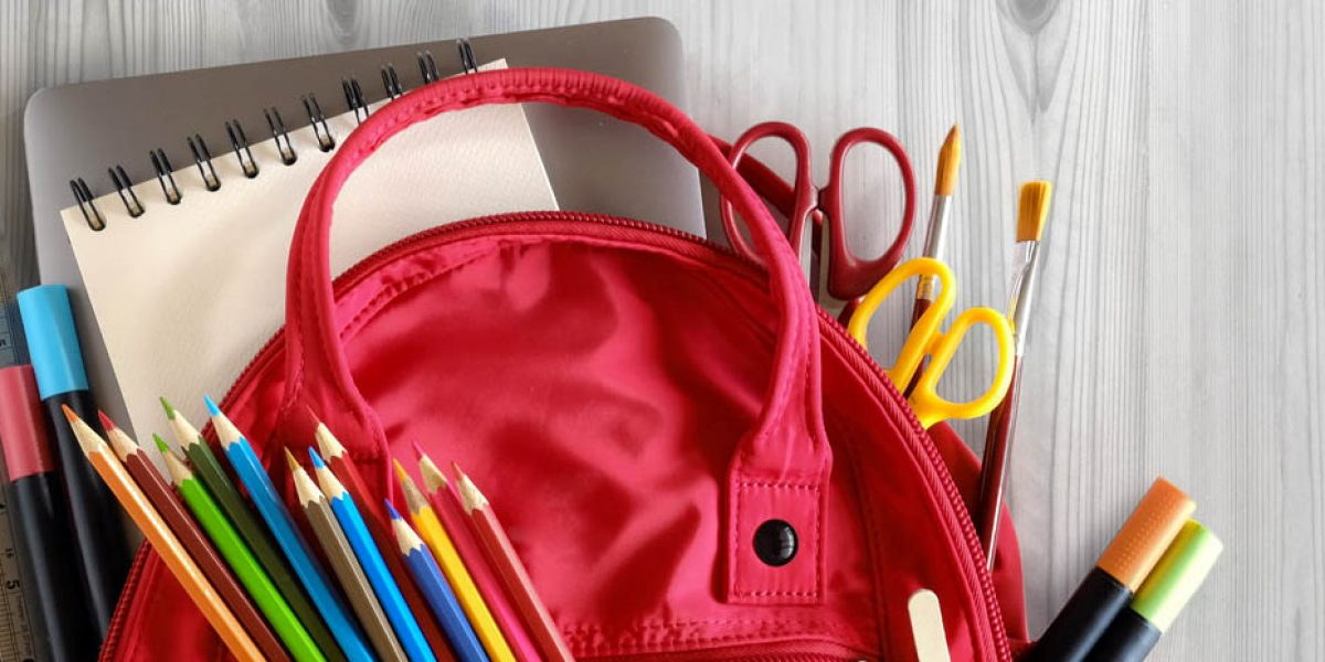 School backpack and school supplies on white wood table background. Back to school concept.